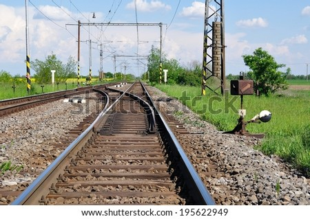 Railway tracks with railroad switch in a rural scene - stock photo