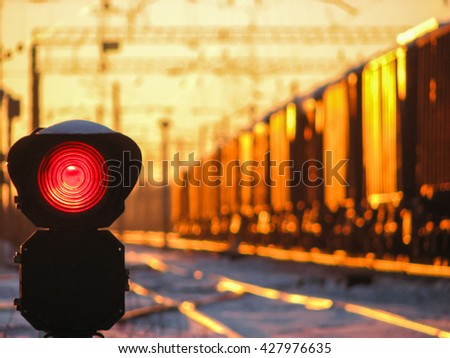 Railway traffic light at sunset shows red signal on railway. Red light. Moving train on the background. - stock photo