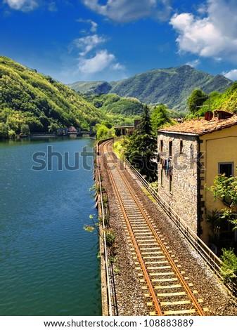 Railway with River, Sky and Vegetation, Tuscany, Italy - stock photo