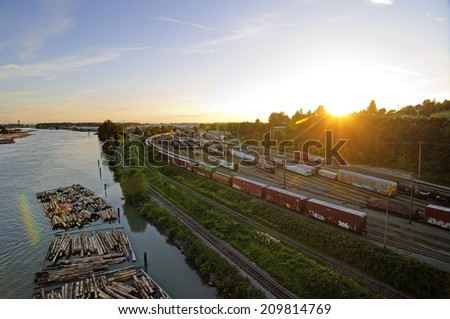 railways by a river at sunset - stock photo