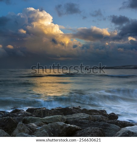 Rain-bearing clouds hang over the horizon casting reflections in the still waters off the Dorset coastline - stock photo
