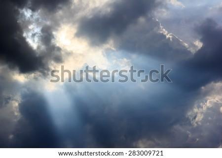 rain cloud and sun beam after storm - stock photo