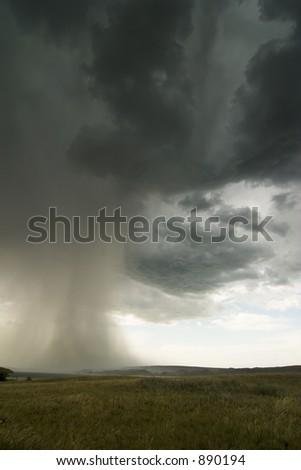 Rain clouds on the horizon over a Saskatchewan landscape. - stock photo