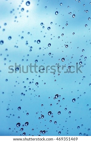Rain drop on clear glass window, blue cold color tone