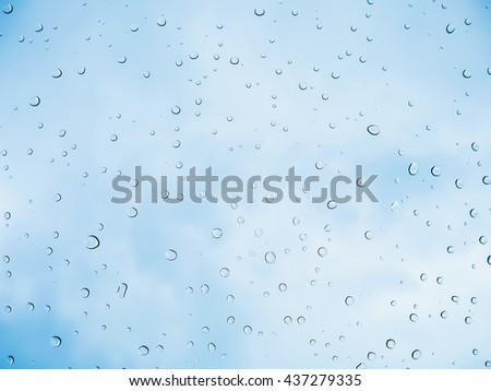Rain drop stick at glass window over blue sky background