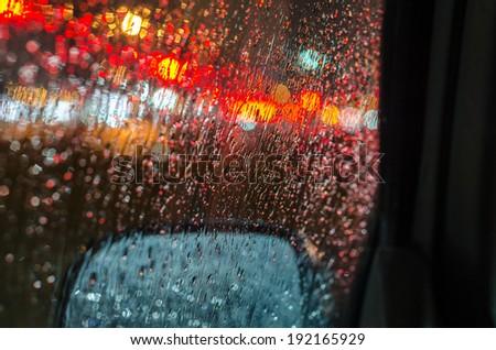 Rain drops at night on vehicles window - stock photo