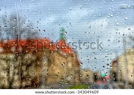 Rain drops covering window glass and clogy sky