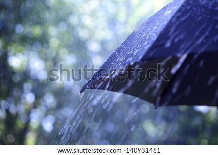 Rain drops falling from a black umbrella - stock photo