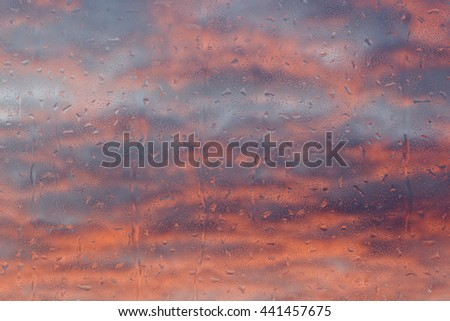rain drops on a window in front of a cloudy sky (3d illustration) - stock photo