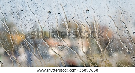 Rain Drops on a Window with a Blurred Background - stock photo