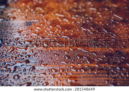 Rain drops on a wooden surface, close-up, on a rainy day, soft-focus - stock photo