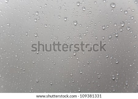 rain drops on black car roof/rain drops on car window - stock photo