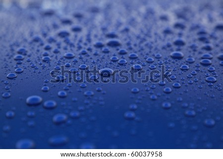 rain drops on blue car body, shallow focus - stock photo