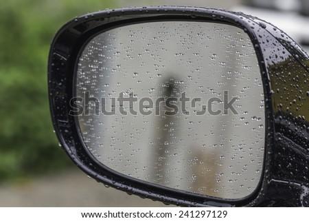 Rain drops on car side view mirror  - stock photo