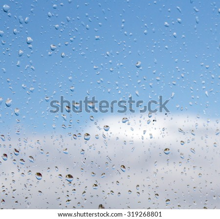 rain drops on glass with blue sky white clouds