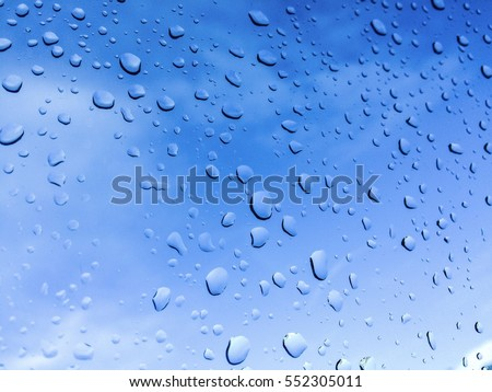 Rain drops on glass with Clear Blue Sky
