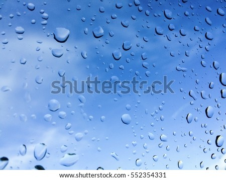 Rain drops on glass with Clear Blue Sky or Water drops of rain on blue glass background