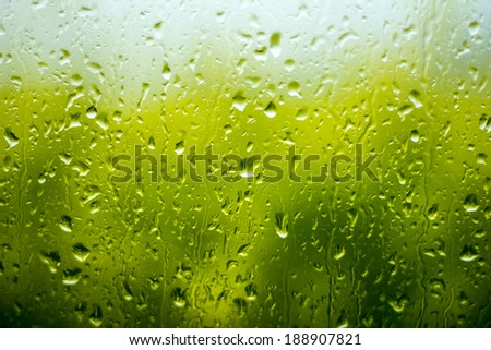 Rain drops on the window on the green background. - stock photo