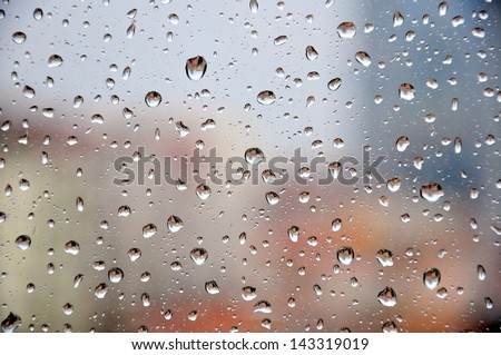 rain drops on window against buildings  - stock photo