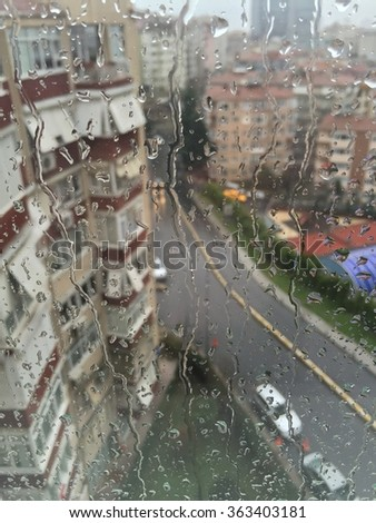 rain drops on window against buildings - stock photo