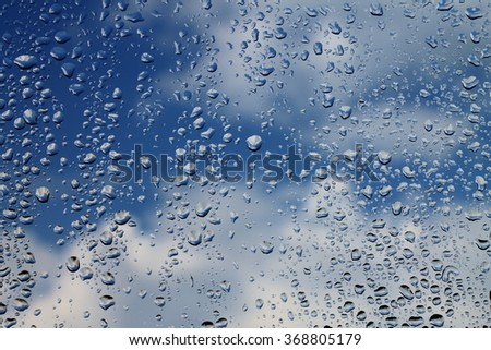 Rain drops on window with blue cloudy sky in background