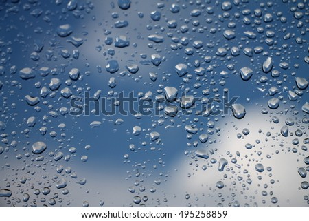 Rain drops on window with blue cloudy sky in background , spring rainy day