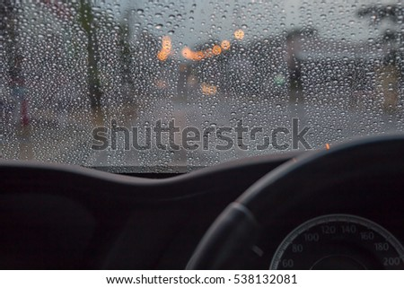 Rain drops on window with road light bokeh, night storm raining car driving concept.