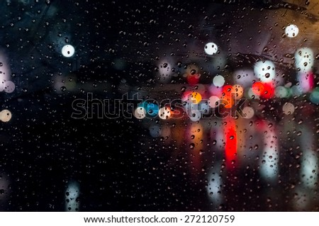 Rain drops on window with street bokeh lights - stock photo