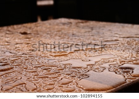 Rain drops on wooden table after rain (shallow DOF)