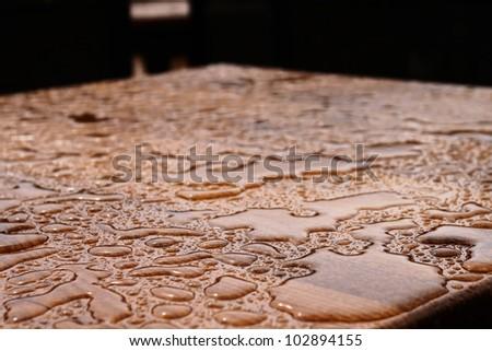 Rain drops on wooden table after rain (shallow DOF) - stock photo