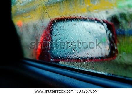 Rain drops rolling on window, and a red car side view mirror on a background, close up - stock photo