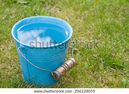 Rain falling into a full bucket of water - stock photo