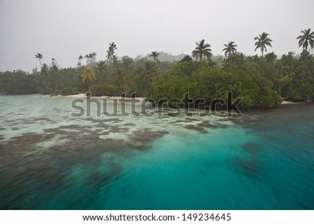 Rain falls on a diverse coral reef fringing a lush, tropical island in the Solomon Islands.  This area is found within the Coral Triangle and is high biological diversity. - stock photo