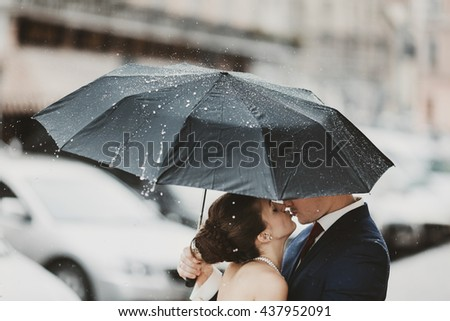Rain falls on the umbrella which hides a kissing couple