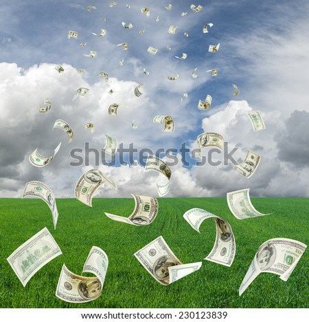 Rain from falling dollars from the sky on the gree field - stock photo