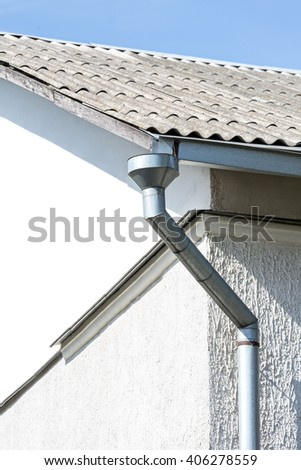 rain gutter and downspout on corner of old house - stock photo