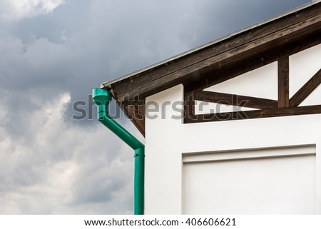 rain gutter and downspout on wall of old house - stock photo