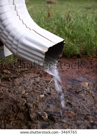 rain gutter draining water away from a residence - stock photo