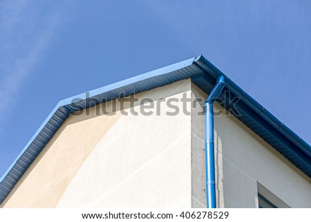 rain gutter on house with blue sky in the background - stock photo