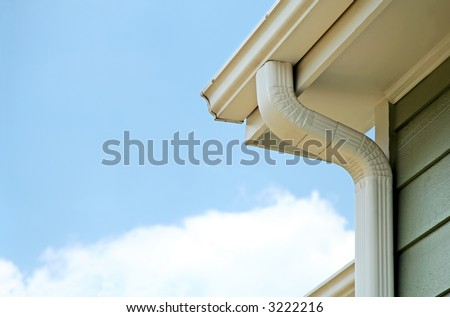 Rain gutters on a home. There is a blue sky with a fluffy white cloud in the background. - stock photo