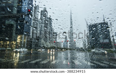 Rain in Dubai, and other skyline seen as blur view behind. - stock photo