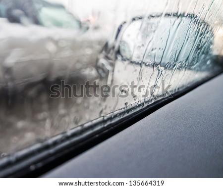 Rain on a car mirror and window - stock photo