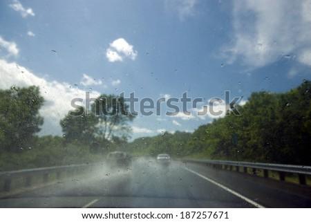Rain on windscreen after rain storm on a sunny day - stock photo