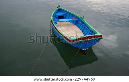 Rain ,silence and a lonely boat - stock photo