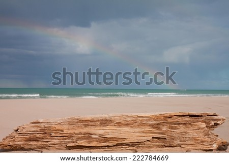 rain storm out at sea with white sandy beach in the foreground  - stock photo