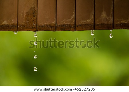 Rain water droplets coming down from rusted metal roof, selective focus with shallow depth of field, blur garden green background