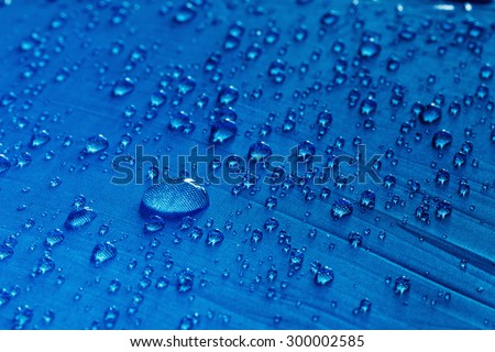 Rain Water droplets on blue fiber waterproof fabric - stock photo