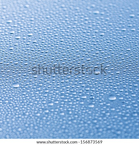 rain water drops lotus effect on blue background - stock photo