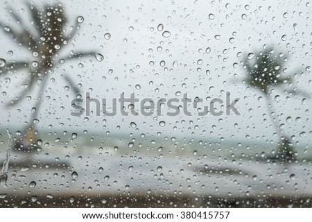 Rain water drops on a glass surface beach background, Abstract Backdrop