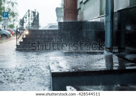 Rain water flowing from metal downspout during a flood. concept of protection against heavy rains. - stock photo